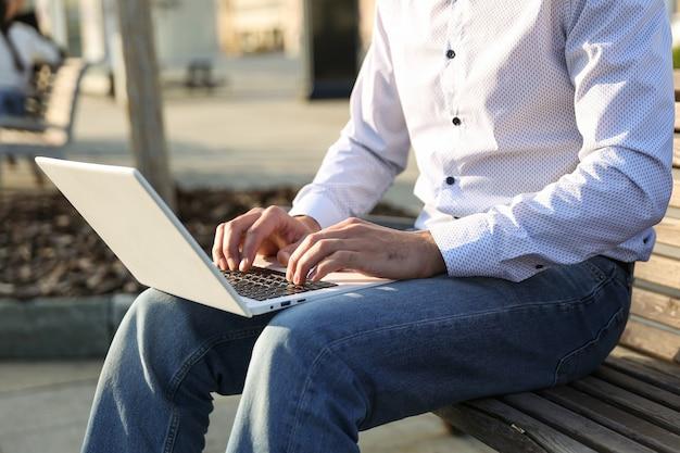 Mężczyzna pisze na laptopie na zewnątrz z bliska