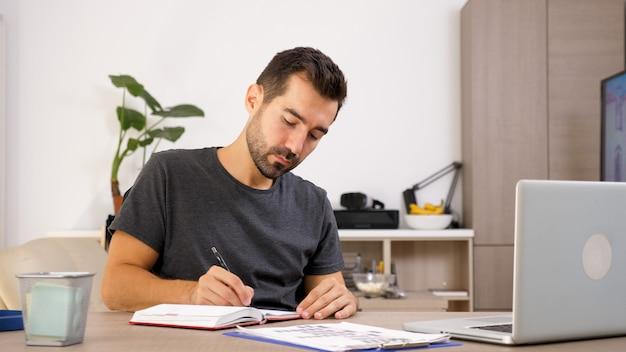 Mężczyzna pisze na notebooku przy biurku. przenoszenie myśli na papier.