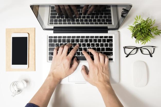 Mężczyzna pisze na swoim laptopie. widok z góry, płaski układ.
