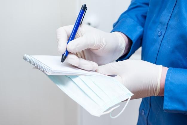 Mężczyzna pisze notatkę w zeszycie podczas epidemii koronawirusa, w rękawiczkach lateksowych
