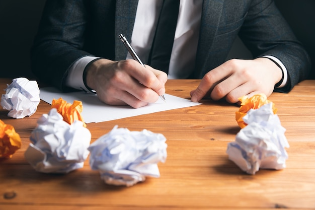 Mężczyzna pisze obok zwoju papieru na szarej powierzchni