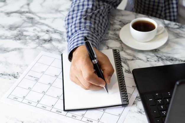 Mężczyzna pisze plany lub cele w notatniku. biurko z notatnikiem, laptopem, kalendarzem, długopisem i filiżanką kawy