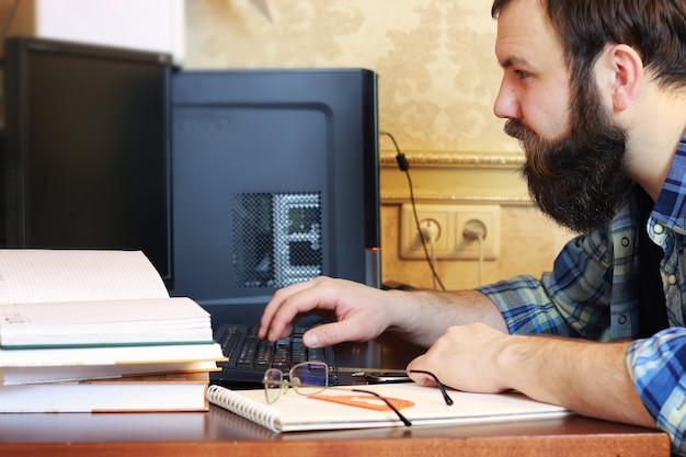 Mężczyzna pisze stół z piórami