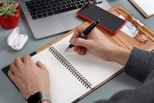 Mężczyzna pisze w porządku obrad na szarym biurku z bliska