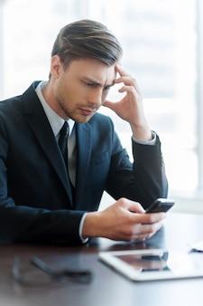 Mężczyzna pisze wiadomość. wesoły młody człowiek korzystający z telefonu komórkowego podczas przerwy na kawę w biurze