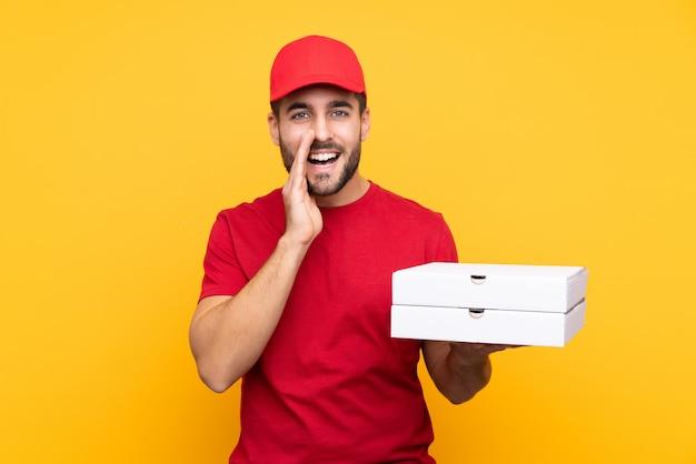 Mężczyzna pizzy chwytający pudełka nad odosobnioną ścianą
