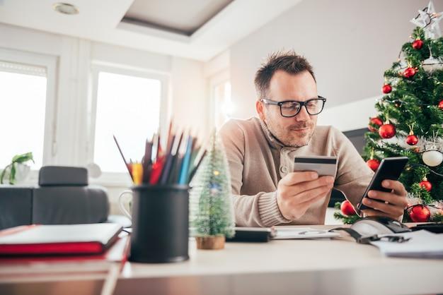 Mężczyzna płaci kartą kredytową na mądrze telefonie