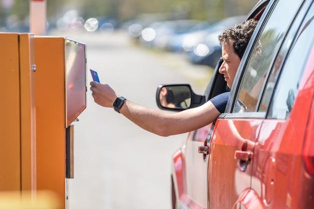 Mężczyzna płaci kartą kredytową za parkowanie w parkometrze