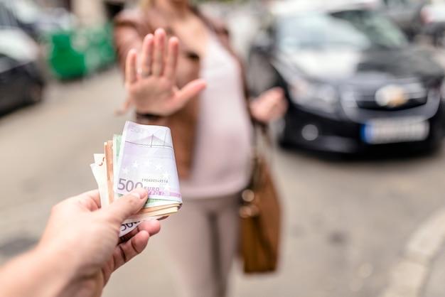 Mężczyzna płaci kobietę za seks. kobieta odmawia przyjęcia łapówki, koncepcji korupcji i przekupstwa