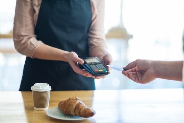 Mężczyzna płaci rachunek przez terminala płatniczego