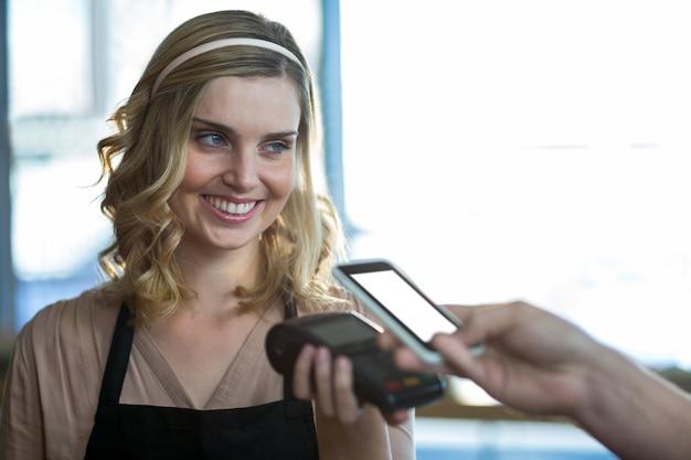 Mężczyzna płaci rachunek za pośrednictwem smartfona za pomocą technologii nfc