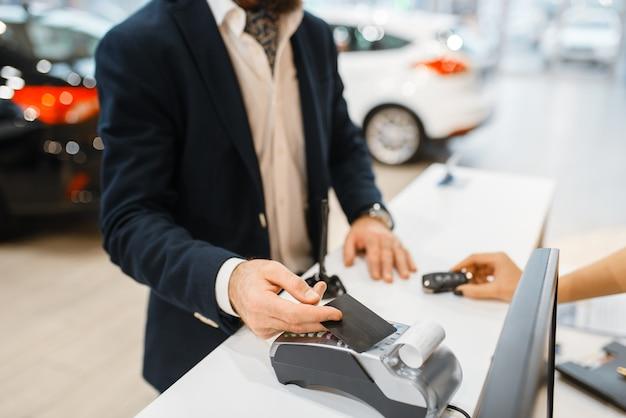 Mężczyzna płaci za zakup nowego auta w salonie samochodowym. klient i sprzedawczyni w salonie samochodowym, mężczyzna kupujący transport, firma dealera samochodowego