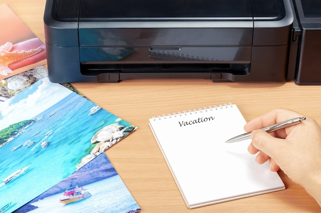 Mężczyzna planujący wakacje ze zdjęciami, które wydrukował po wakacjach. koncepcja planowania wakacji w pięknym miejscu.