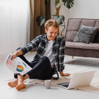 Mężczyzna planuje remont domu przy użyciu laptopa i palety farb