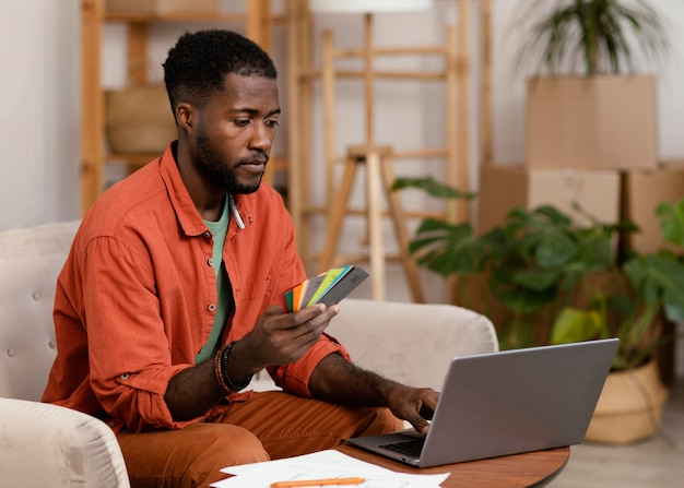 Mężczyzna planuje remont domu przy użyciu laptopa i palety kolorów