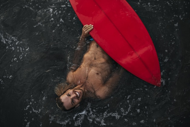 Mężczyzna pływa z czerwoną deską surfingową