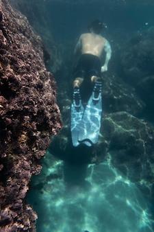 mężczyzna pływający pod oceanem