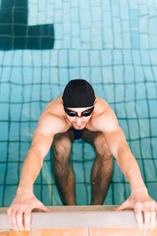 Mężczyzna pływak pod dużym kątem w pozycji gotowej