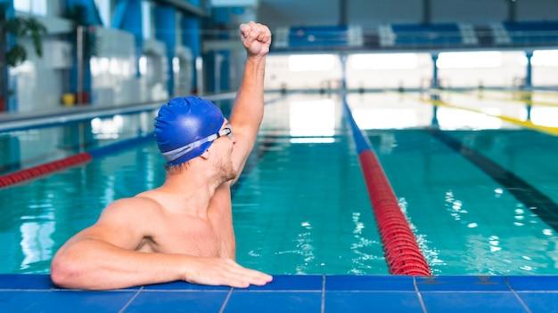 Mężczyzna pływak podnosi rękę