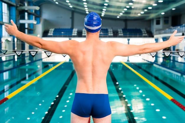 Mężczyzna pływak rozgrzewa się przed pływaniem
