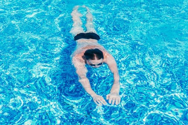 Mężczyzna pływanie pod wodą w koncepcji wakacji letnich basen