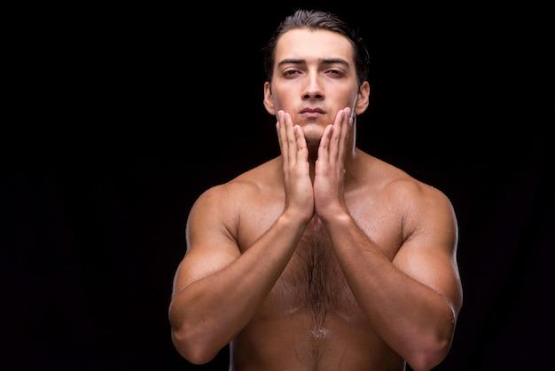 Mężczyzna po brać prysznic na ciemnym tle