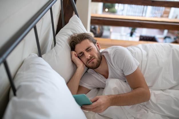 Mężczyzna po przebudzeniu aktualizuje swój kanał przy użyciu smartfona