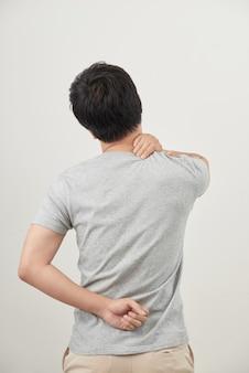 Mężczyzna pociera swoje bolesne plecy z bliska. biznesmen trzyma jego dolną część pleców. ulga w bólu, koncepcja chiropraktyki