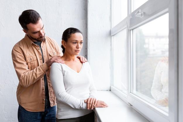 Mężczyzna pociesza smutną kobietę na sesji terapii grupowej, patrząc przez okno