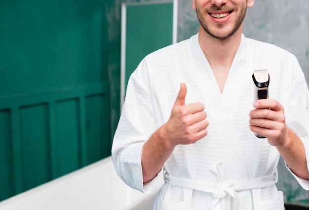 Mężczyzna podając kciuki i trzymając trymer