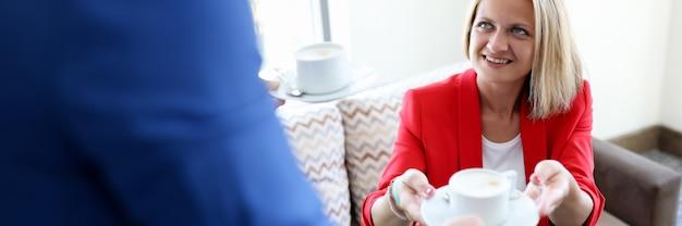 Mężczyzna podaje filiżankę kawy uśmiechniętej kobiecie