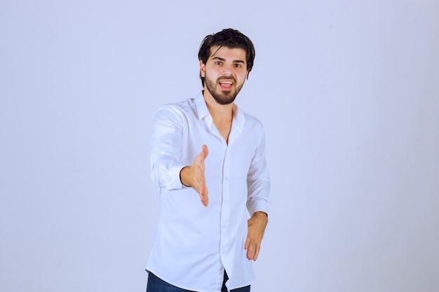 Mężczyzna podaje rękę do przywitania się i przedstawienia się.