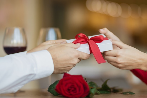 Mężczyzna podaje swojej dziewczynie białe pudełko z czerwoną wstążką. młoda kobieta bierze prezent od swojego chłopaka. dwa kieliszki wina i róża na stoliku w kawiarni. koncepcja walentynki.