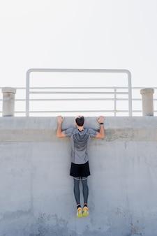 Mężczyzna podciągający się na zewnątrz chwyta ścianę z czystym niebem w południe