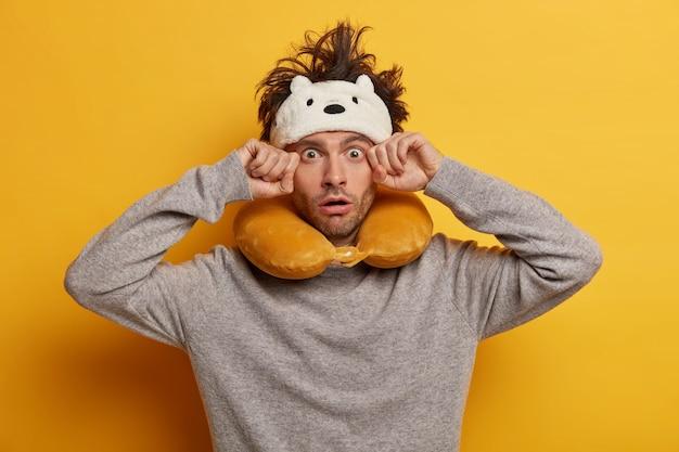 Mężczyzna podczas podróży nosi poduszkę podróżną do spania