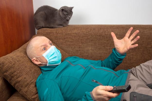 Mężczyzna poddany kwarantannie w domu z maską medyczną na twarzy leży na kanapie i ogląda telewizję obok szarego kota. odpocznij podczas epidemii koronawirusa.