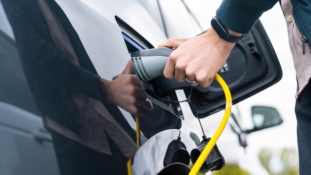 Mężczyzna podłącza ładowarkę do samochodu elektrycznego na stacji ładującej