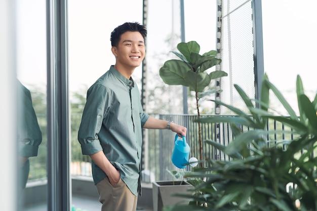 Mężczyzna podlewania roślin w pojemniku na balkonowym ogrodzie