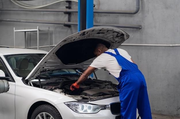 Mężczyzna podniósł maskę samochodu i sprawdza silnik
