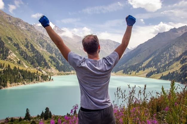 Mężczyzna podniósł ręce do nieba na tle górskiego jeziora