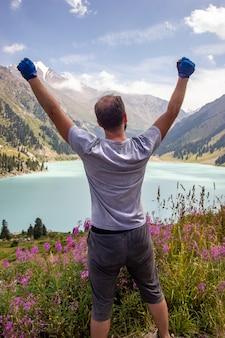 Mężczyzna podniósł ręce na wielkie jezioro almaty w górach tienshan w regionie ałmaty w kazachstanie