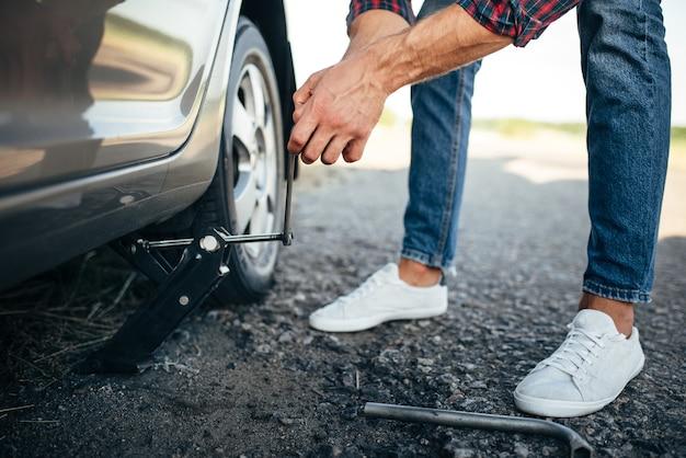 Mężczyzna podniósł zepsuty samochód, wymiana koła