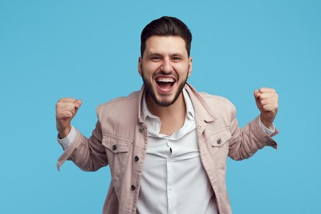 Mężczyzna podnosi pięści z radości świętuje zwycięstwo na białym tle nad niebieską ścianą