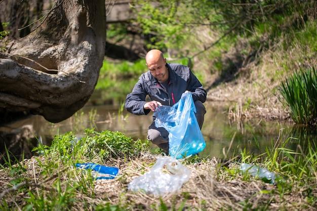 Mężczyzna podnosi plastikową butelkę, zbiera śmieci na leśnej planecie sprzątającej, pomaga środowisku charytatywnemu zbierania śmieci