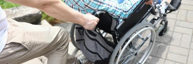 Mężczyzna podnosi po schodach kobietę na wózku inwalidzkim