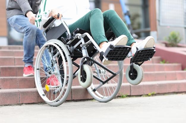 Mężczyzna podnosi wózek inwalidzki po schodach z kobiecą adaptacją schodów dla koncepcji osób niepełnosprawnych
