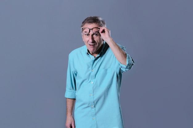 Mężczyzna podnosząc okulary