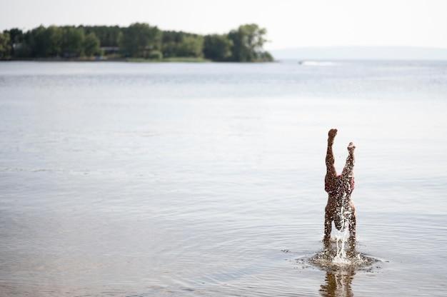 Mężczyzna podnosząc ręce w jeziorze