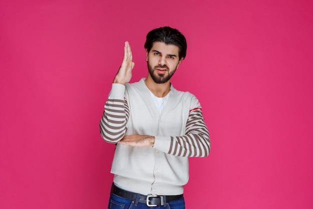 Mężczyzna podnosząc rękę i prosząc o uwagę.