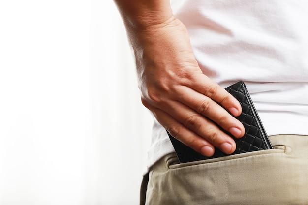 Mężczyzna podnoszący czarną torebkę z tyłu